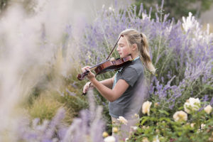 United States,Teenage girl standing among flowering roses and shrubs, playing a violin,